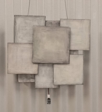 6 overlapping canvas panels painted slightly different shades of gray, all squared up.